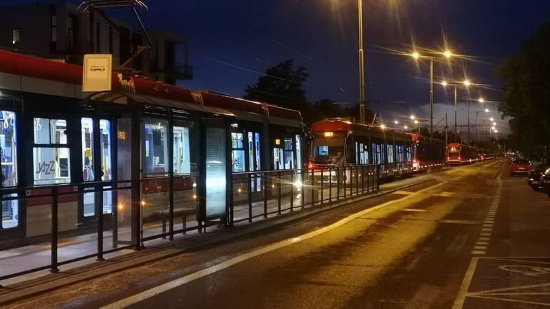 Ciemno, po lewej przystanek tramwajowy. Na torach stoi tramwaj, za nim kolejne. Obok na prawo ulica. Między torami i ulicą stoją słupy oświetleniowe z zapalonymi lampami.