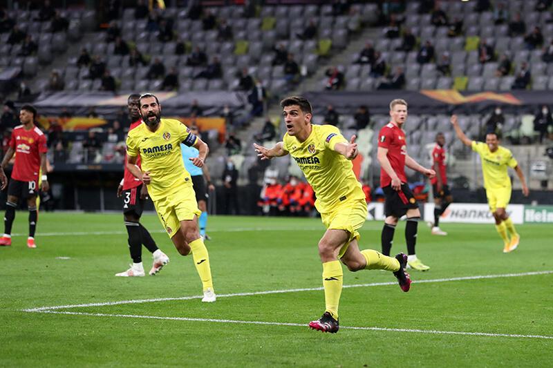 Piłkarz w żółtym stroju biegnie ciesząc się z gola. Obok inny w żółtym stroju. Dalej kilku w czerwonych koszulkach