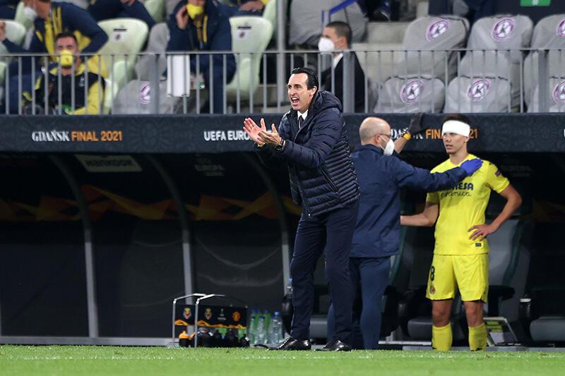 Mężczyzna w kurtce stoi przy linii boiska i klaszcze (trener Villarreal), za nim odwrócony plecami łysy mężczyzna w kurtce, trzyma prawą dłoń w rękawiczce na klatce piersiowej piłkarza w żółtym stroju z obandażowanym czołem