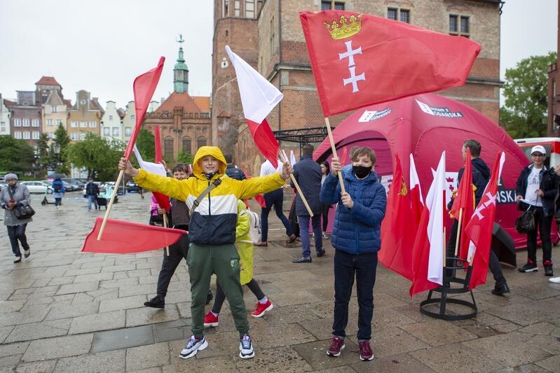 Kilka osób pozuje do zdjęcia z flagami Gdańska i flagami narodowymi. Za nimi widać mur Katowni i zabytkową Strzelnicę św. Jerzego