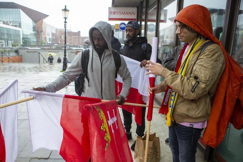 Dwaj Etiopczycy i dwaj Turcy - studenci z Białegostoku - z przyjemnością przyjęli podarowane im flagi