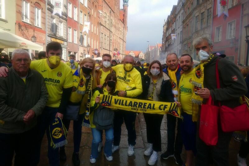 Grupa około dziesięciu kibiców pozuje do zdjęcie na środku ulicy Długiej. Osoby znajdujące się pośrodku trzymają w rękach rozwinięty żółto-niebieski szalik Villarrealu. Lidia jest trzecia od lewej, Jesus - drugi od prawej