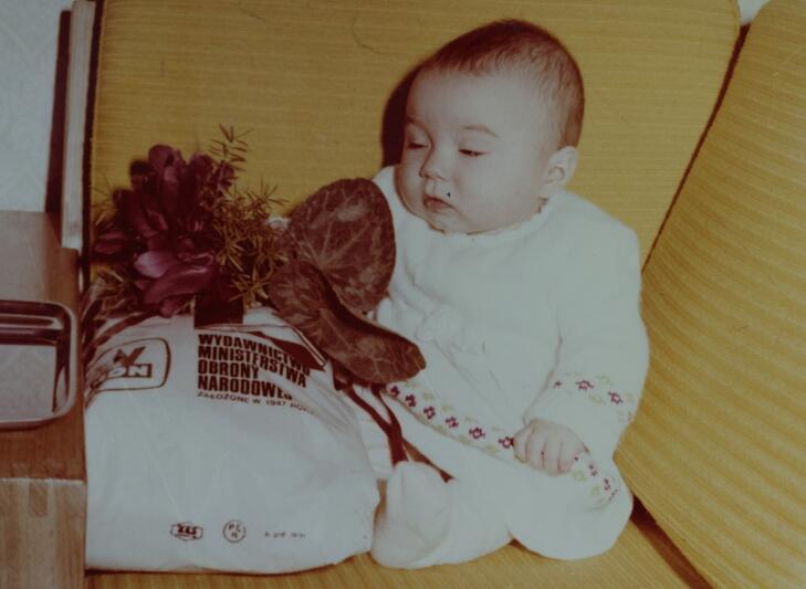 Mała gdańszczanka po uroczystości nadania imienia w Pałacu Ślubów w Gdańsku, siedzi prawdopodobnie wśród swoich prezentów, zdjęcie pochodzi z kroniki Urzędu Stanu Cywilnego w Gdańsku