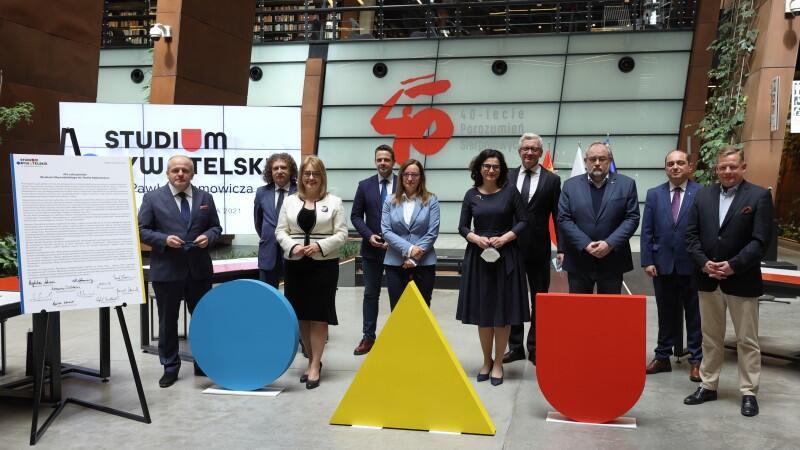 dziesięć osób stoi na scenie, na pierwszym planie kolorowe geometryczne figury
