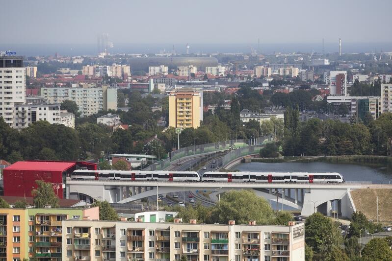 Widok Gdańska ze wzgórza morenowego na Niedźwiedniku. Pośród zieleni widać liczne bloki, domy mieszkalne i gmachy użyteczności publicznej. Na pierwszym planie widać bloki i przejeżdżający w pewnej odległości za nimi - na kolejowym wiadukcie - srebrzysty szynobus Pomorskiej Kolei Metropolitalnej