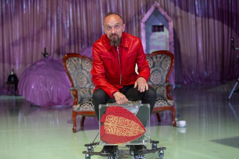 Mężczyzna w średnim wieku, ma brodę, siedzi w czerwonej skórzanej na stylizowanej kanapie ustawionej pośrodku sceny.