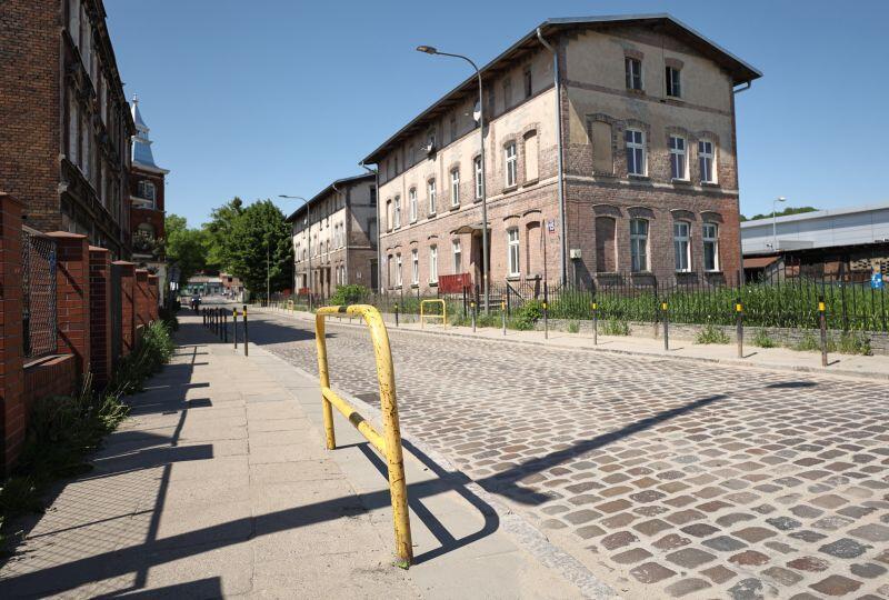 ulica brukowana, stary chodnik i poręcz, w tle stare budynki