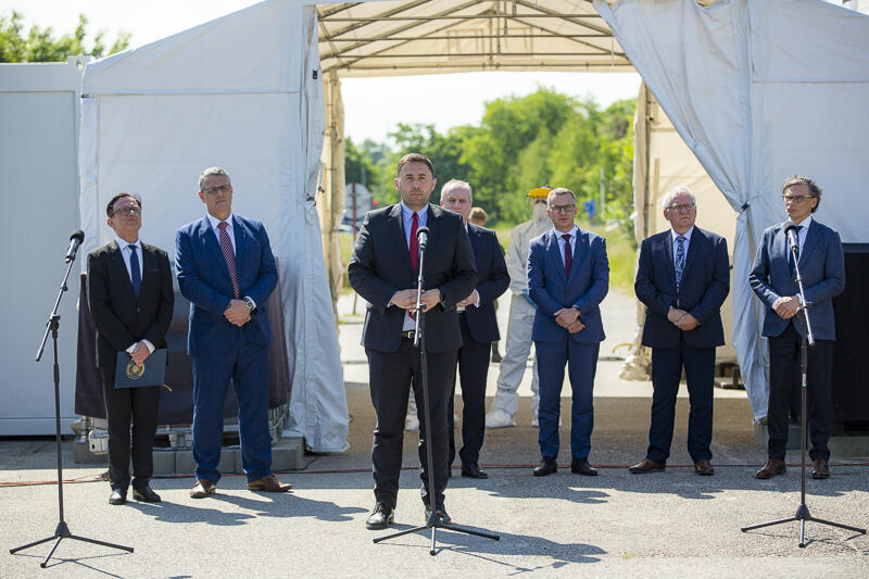 Mężczyźni w średnim wieku, w garniturach, stoją przed mikrofonami