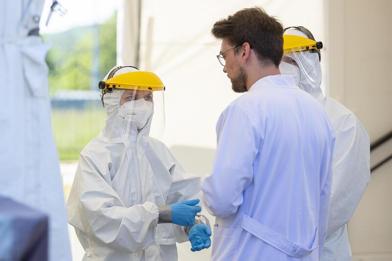 Młody mężczyna w białym fartuchu stoi tyłem, przed nim dwie osoby w medycznych kombinezonach