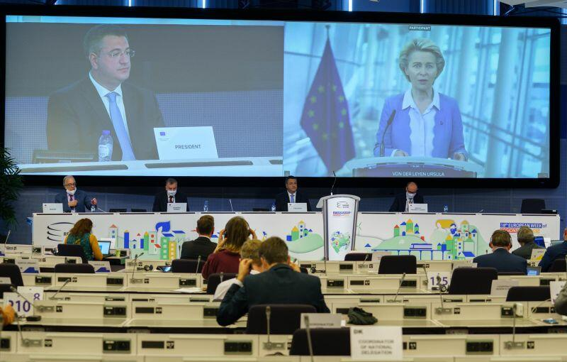 Przewodnicząca Komisji Europejskiej Ursula von der Leyen. Obok na drugim ekranie przewodniczący Komietetu Regionów Apostolos Tzitzikostas