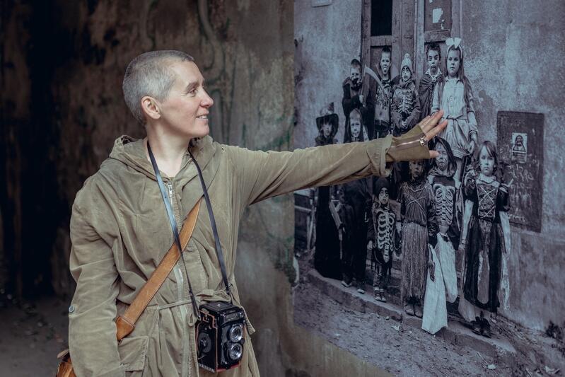 kobieta dotyka ręką muru, na którym wydrukowane jest zdjęcie portret - dzieci