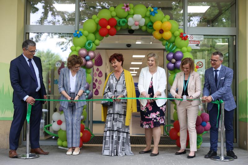 Kilka osób elegancko ubranych stoi przed drzwiami z balonikami