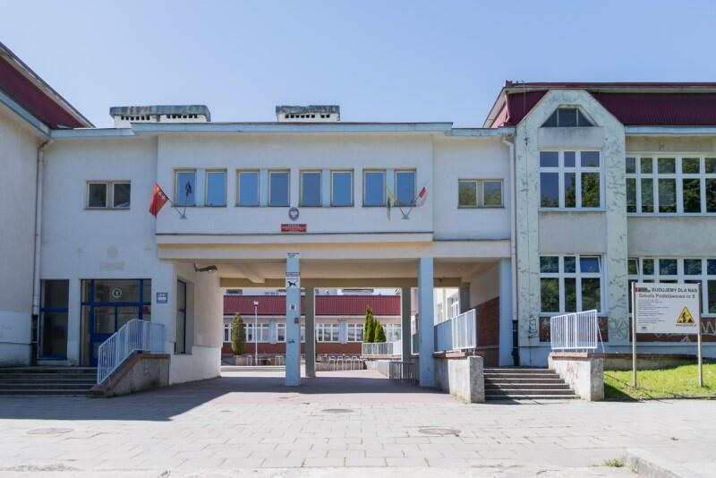 Budynek jednej z gdańskich szkół. Zdjęcie wykonano przy słonecznej pogodzie. Widać wejście na dziedziniec szkoły, które znajduje się między dwoma skrzydłami budynku, pod łącznikiem korytarza biegnącego na pierwszym piętrze. W środkowej części łącznika jest czerwona tablica z nazwą szkoły i tablica z godłem państwowym. Na prawo i lewo od tablic wiszą flagi: Polski, Gdańska i Unii Europejskiej