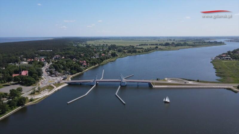 Widać Martwą Wisłę, która przebiega lekkim łukiem w prawo, w głąb obrazu. W poprzek rzeki znajduje się most, po którym jadą auta. Po prawej, przed mostem, widać sporej wielkości jacht. Po lewej stronie rozciąga się Wyspa Sobieszewska z zabudowaniami Sobieszewa. Dalej są lasy, które kończą się w miejscu, gdzie są nadmorskie plaże. Po horyzont widać Zatokę Gdańską