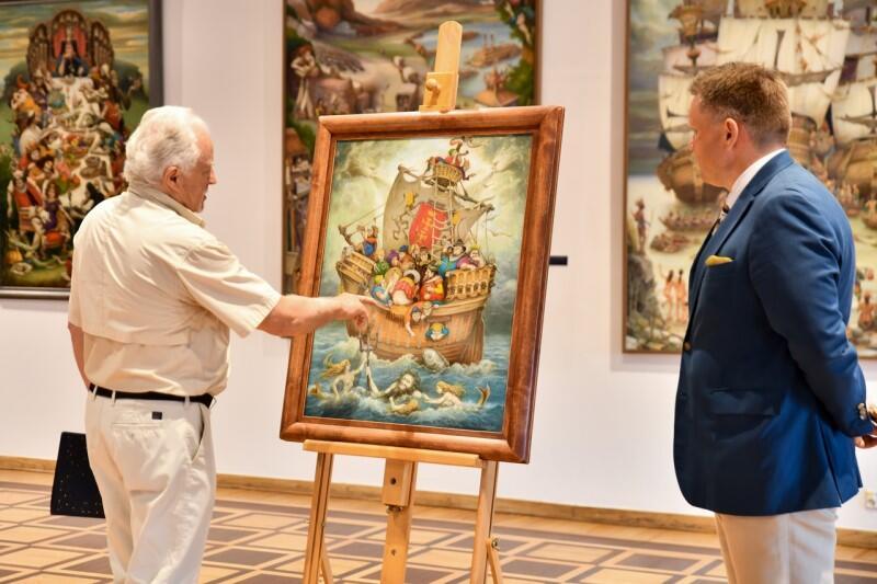 Strszy mężczyna, siwe włosy, stoi, wskazuje cos na obrazie, który stoi na sztalugach w środku, obok stoi tyłem mężczyzna w średni wieku