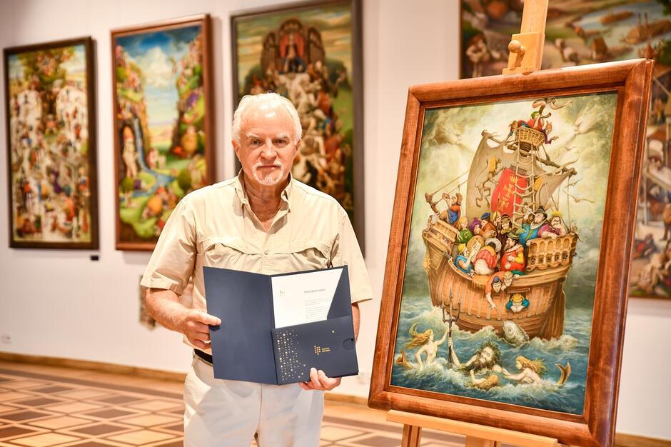 Włodzimierz Szpinger trzyma w dłoniach teczkę z zestawem Darczyńcy Muzeum Gdańska. Stoi obok obrazu postawionego na sztaludze.