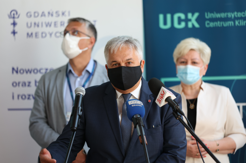 Trzy osoby w maseczkach dwóch mężczyzn, jedna kobieta stoją przed mikrofonami, w maseczkach na twarzy