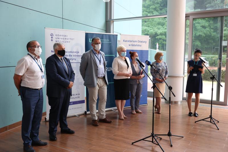 Siedem osób w róznym wieku, kobiet i mężczyzn stoi przed mikrofonami