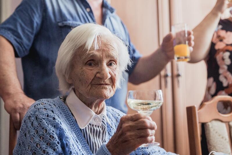 Starsza kobieta trzyma w ręku kieliszek