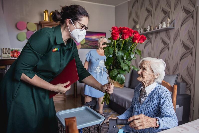 Bardzo stara kobieta siedzi, kobieta w średnim wieku wręcza jej kwiaty