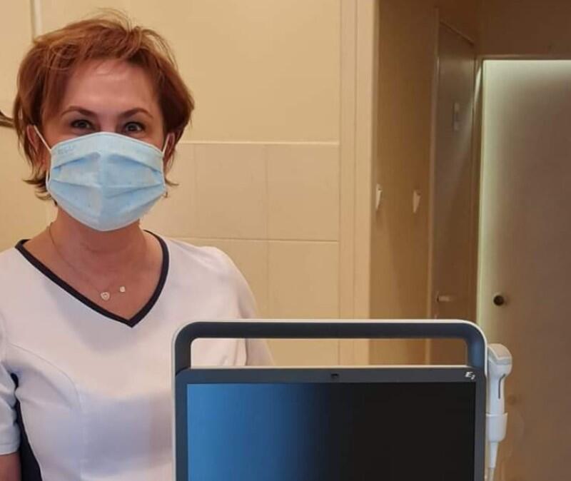 Kobieta w średnim wieku w maseczce, w lekarskim fartuchu