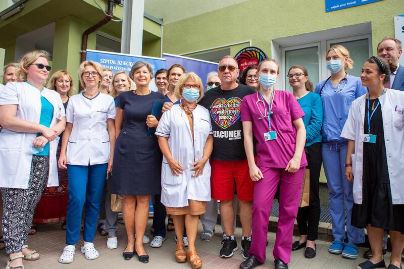 Kilkanaście osób, część w strojach lekarskich, niektórzy w maseczkach pozują do zdjęcia