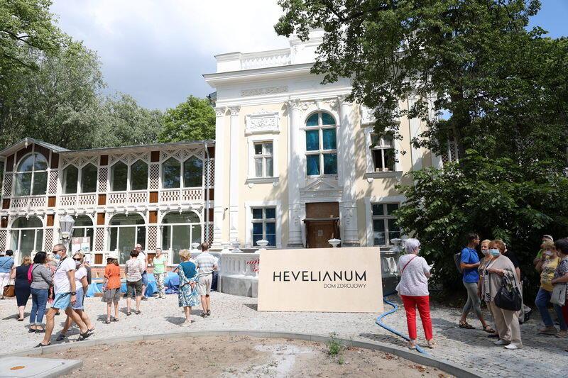 Duży ładny jasny budynek z końca XIX wieku. Przed nim ludzie i plansza z napisem HEVELIANUM DOM ZDROJOWY, obok duże drzewo