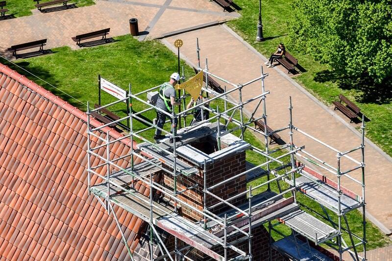 Montaż chorągwi wiatrowej na dachy Wielkiego Młyna, 12 maja 2021 r. Na pozłacanym toporze wycięty w metalu napis: Renov. 2021.