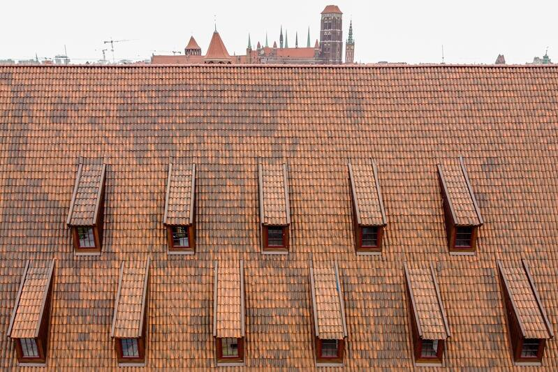 Dach Wielkiego Młyna - postarzony z rozmysłem, z użyciem dachówki o kształcie nawiązującym do historycznej mniszki losowo barwionej ciemniejszą masą w trakcie produkcji