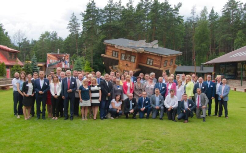 Kilkadziesiat osób stoi przed drewnianym domem