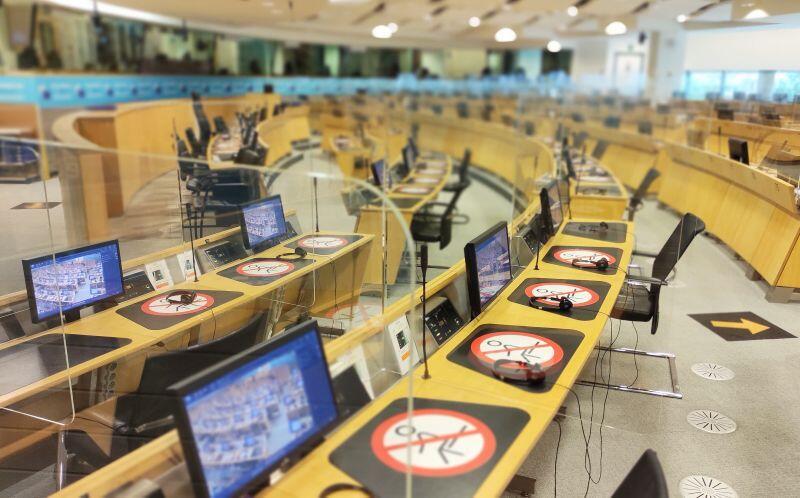 Jedna z sal obrad w siedzibie Europejskiego Komitetu Regionów. Stanowiska dla uczestników oddzielono plastikowymi zasłonami, niektóre miejsca wyłączono z użytkowania