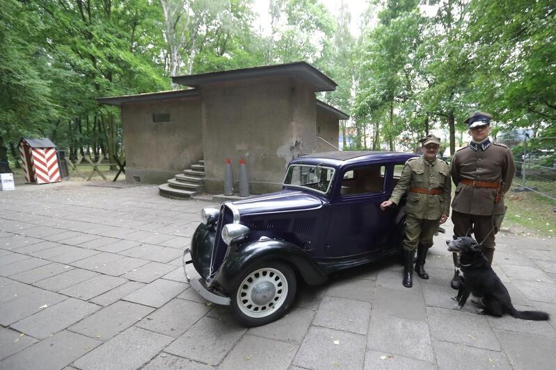 Na zdjęciu, nieco po prawej, mamy zabytkowy samochód koloru granatowego oraz stojących na prawo od niego dwóch mężczyzn w przedwojennych polskich mundurach oficerów Wojska Polskiego. U stóp mężczyzn siedzi pies. W głębi znajduje się betonowy budynek Wartowni nr 1 i zieleń lasu