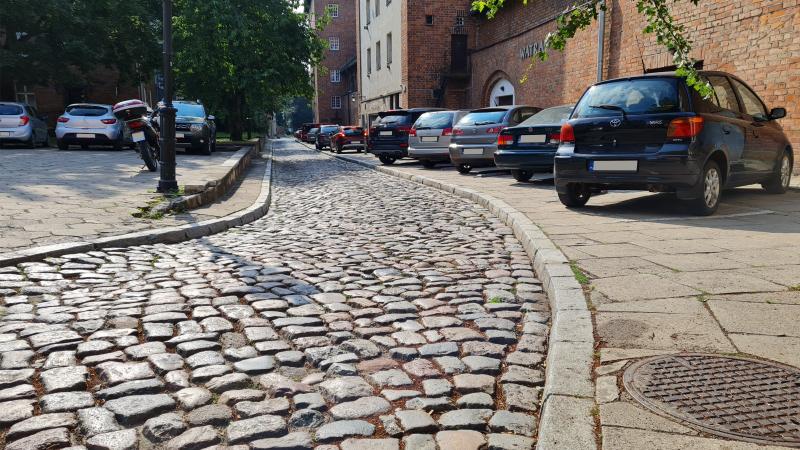 Widok brukowanej uliczki, biegnącej wzdłuż ceglanych murów, które są po prawej. Po lewej znajduje się parking dla samochodów osobowych. Auta są zaparkowane po obu stronach ulicy