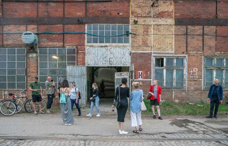 ściana z cegły, a w niej otwarte, metalowe drzwi, ludzie stoją przed wejściem