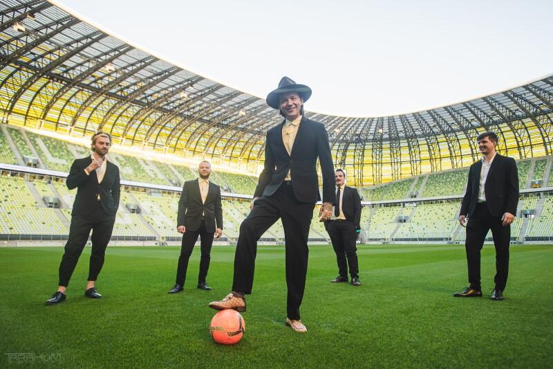 Wojtek Mazolewski z zespołem na murawie gdańskiego stadionu. Lider w pewnej chwili zdjął kapelusz i wykorzystał tę okazję, by zrobić popis piłkarskich umiejętności