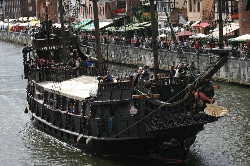 Zdjęcie przedstawia statek płynący wzdłuż nabrzeża Motławy w zabytkowej części Gdańska. Nabrzeże z turystami, kawiarniami, parasolami i punktami sprzedaży pamiątek - widać po prawej stronie. Statek skierowany jest dziobem wzdłuż nurtu rzeki, nieco w prawo na zdjęciu. Czarna Perła to kuter, który został przerobiony na atrapę pirackiego statku, z masztami i ozdobami charakterystycznymi dla żaglowców sprzed trzech, czterech stuleci