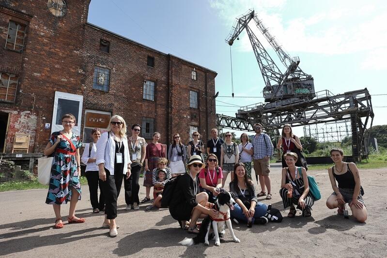 Pozująca do zdjęcia grupa kilkunastu osób, na tle jednej z postoczniowych hal produkcyjnych. Po prawej widoczny jest pomalowany na zielono postoczniowy dźwig. Hala jest zabytkowa, zbudowana z czerwonycn cegieł