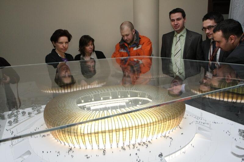 Makieta gdańskiego stadionu pod szkłem. Obok oglądający ją ludzie