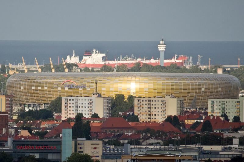Widok z góry: na pierwszym planie budynki handlowe i mieszkalne w tym 10-pietrowe, za nimi i ponad nimi bryła bursztynowego stadionu. Za nim morze i statek handlowy przy brzegu