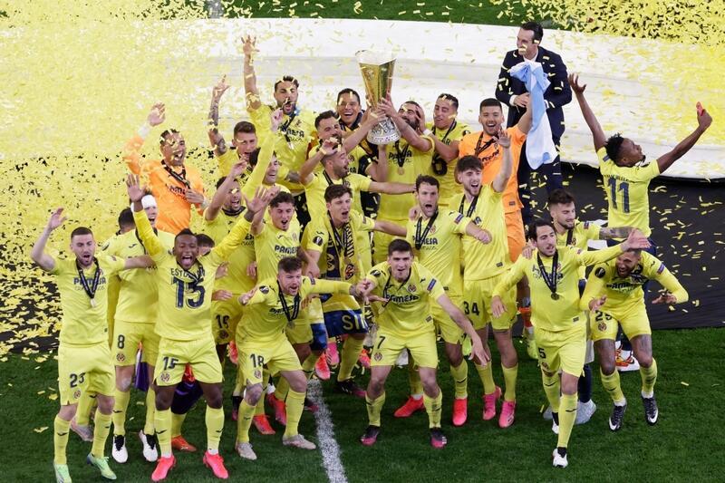 Piłkarze w żółtych strojach ustawienie w kilku rzędach, cieszą się, uśmiechają. Jeden z nich trzyma w dłoniach puchar. Nad nimi i murawą żółte konfetti