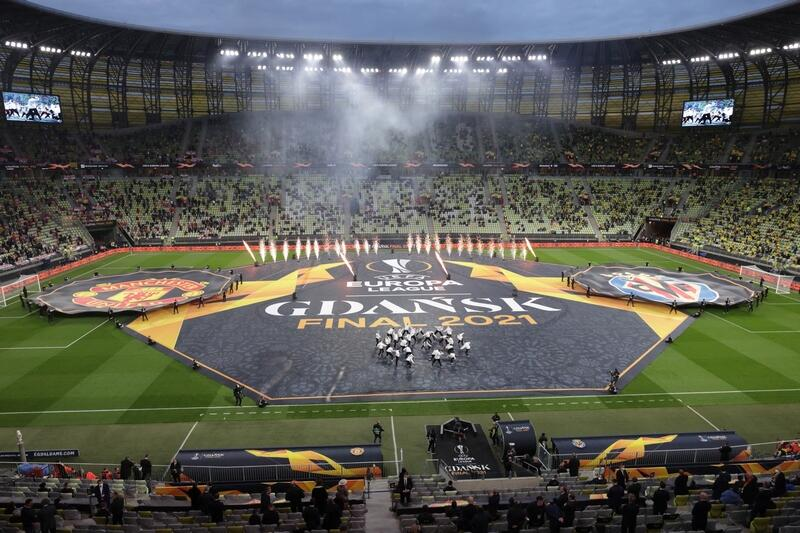 Stadion, na murawie rozłożona wielka płachta: po bokach loga klubów Villarreal i Manchesteru United, w środku napis GDANSK FINAL 2021