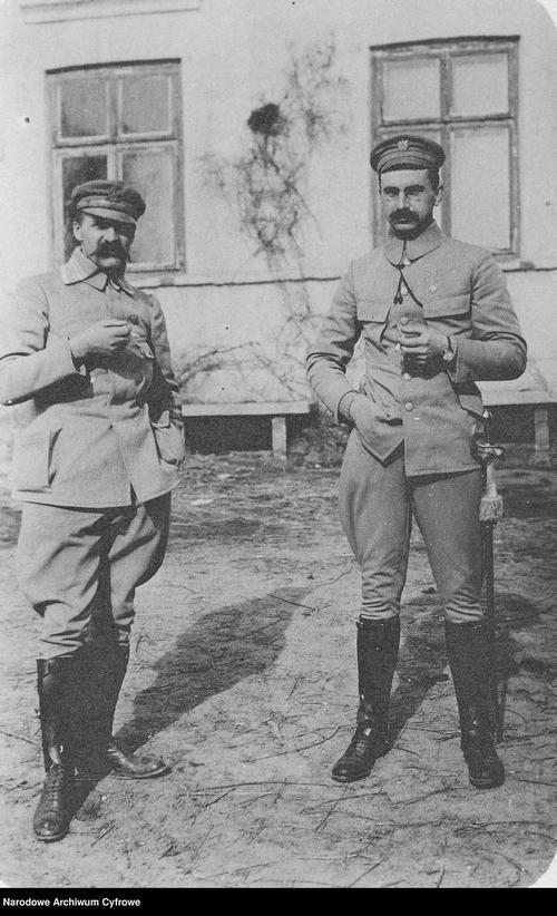 Stare czarno-białe zdjęcie. Dwóch mężczyzn w mundurach wojskowych stroi przed budynkiem. Na głowach mają wojskowe czapki, pod nosem sumiaste wąsy