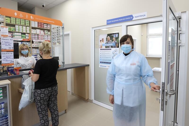 Wnętrze apteki, przy drzwiach stoi kobieta w średnim wieku w białym fartuchu, przy okienku młoda kobieta kupuje