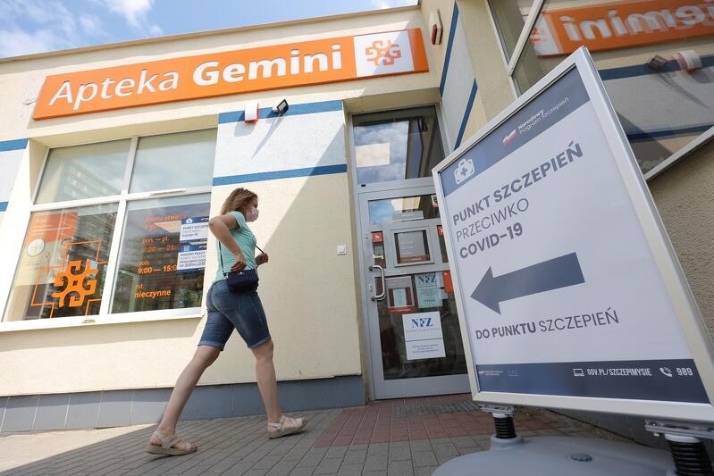 Fragmnet budynku z napisem apteka, otwrte drzwi, w ich kierunku idzie młoda kobieta w maseczce