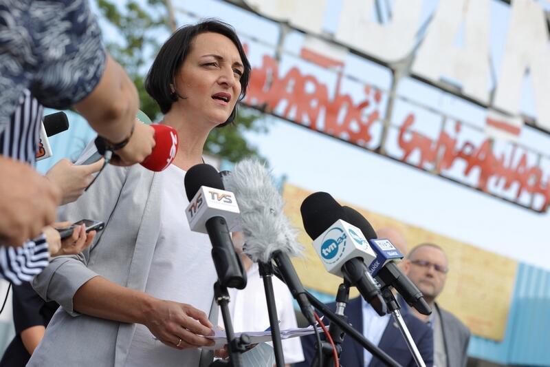 Kobieta w jasnej sukience i marynarce stoi przed mikrofonami dziennikarzy. Za nią fragment bramy stoczni, widoczny napis SOLIDARNOŚĆ