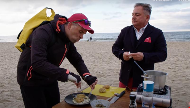 Mężczyzna w średnim wieku na plaży, obok stolik z patelnią i potrawami, drugi mężczyzna próbuje potraw