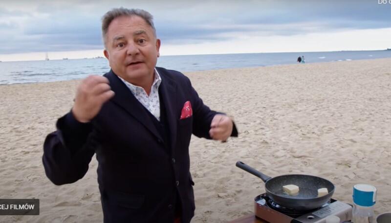 Meżczyzna w średnim wieku na plaży, obok niego polowa kuchenk, na niej patelnia