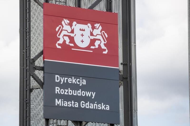 Logo Dyrekcji Rozbudowy Miasta Gdańska w budynku AmberExpo przy ul. Żaglowej 11, gdzie mieści się siedziba jednostki