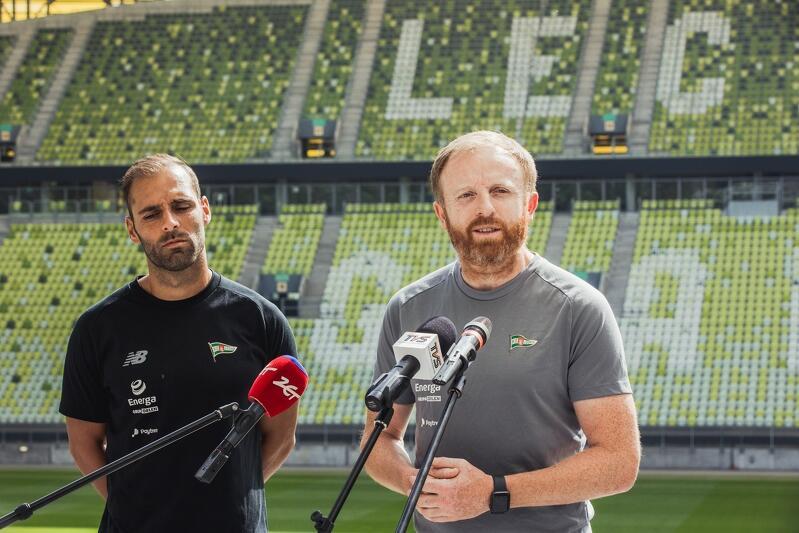 Dwaj mężczyźni stoją na murawie gdańskiego stadionu. Przed Piotrem Stokowcem znajdują się trzy statywy z mikrofonami. Flavio stoi na lewo od trenera