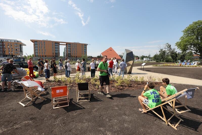 Fragment osiedla, nowoczesny budunek przed nim ziemia zasiana trawą, lezaki, dróżki, stoi grupa ludzi
